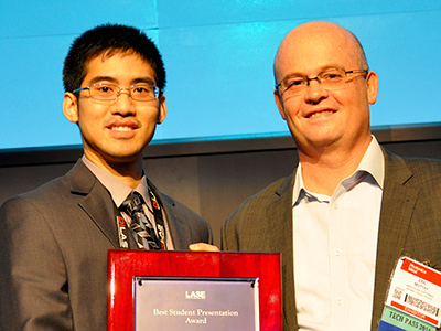 Kenneth Lee receives his first prize in the student competition at Photonics West from Dr. Eric Mottay.