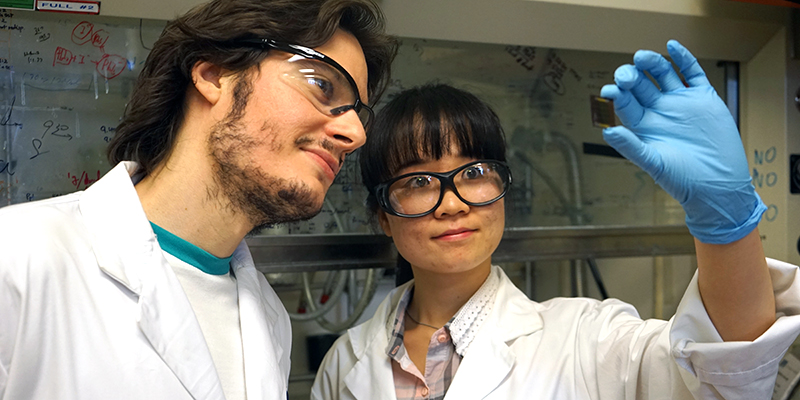 Riccardo Comin (left) and Xiwen Gong examine a prototype device coated with their new hybrid crystal and embeds quantum dots in perovskite.
