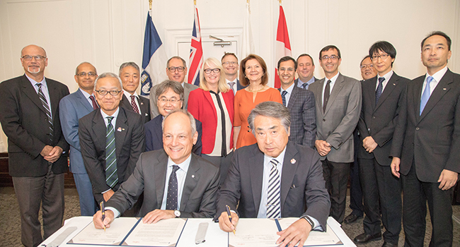 U of T President Meric Gertler, seated centre left, and Shigeru Sasaki, CEO of Fujitsu Laboratories, seated centre right, sign a memorandum of understanding. This marks the first R&D centre opened in Canada by Fujitsu Laboratories, a major engine of research and development in the world's leading innovation clusters such as Silicon Valley, London and Shanghai. (Credit: Lisa Lighbourn)
