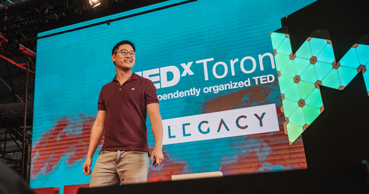 Gimmy Chu stands on stage in front of a TEDX projection