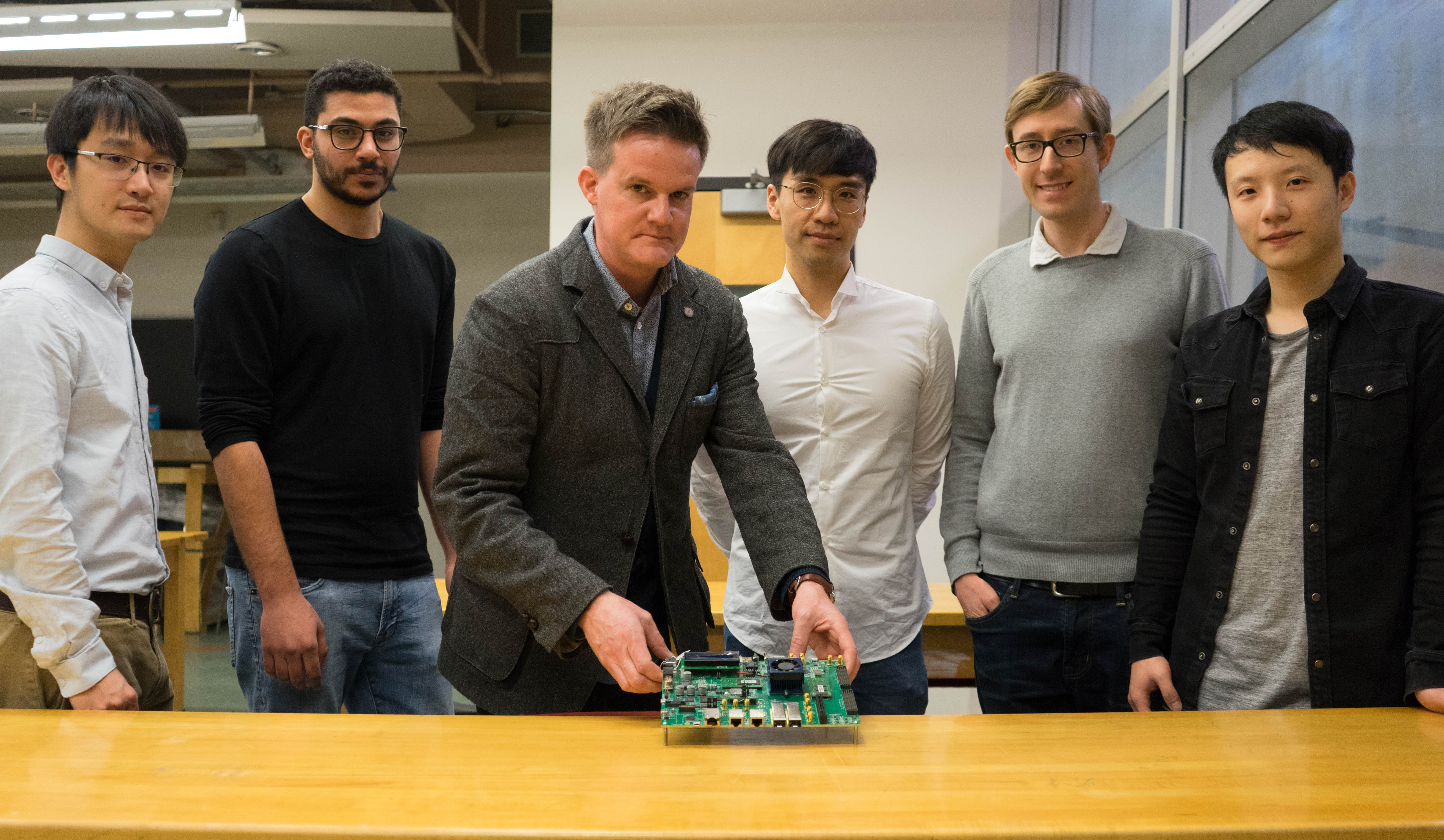 Professor Jason Anderson holds an FPGA board with the LegUp team behind him. Left to right, Zhi Li (CompE 1T3), Omar Ragheb (CompE MEng 1T8), Professor Jason Anderson (ECE), Dr. Jongsok Choi (CompE MASc 1T2, PhD 1T6), Dr. Andrew Canis (CompE PhD 1T5), and Ruolong Lian (CompE 1T3, MASc 1T6) are making it easier for software developers to leverage servers based on FPGAs. (Photo: Jessica MacInnis)
