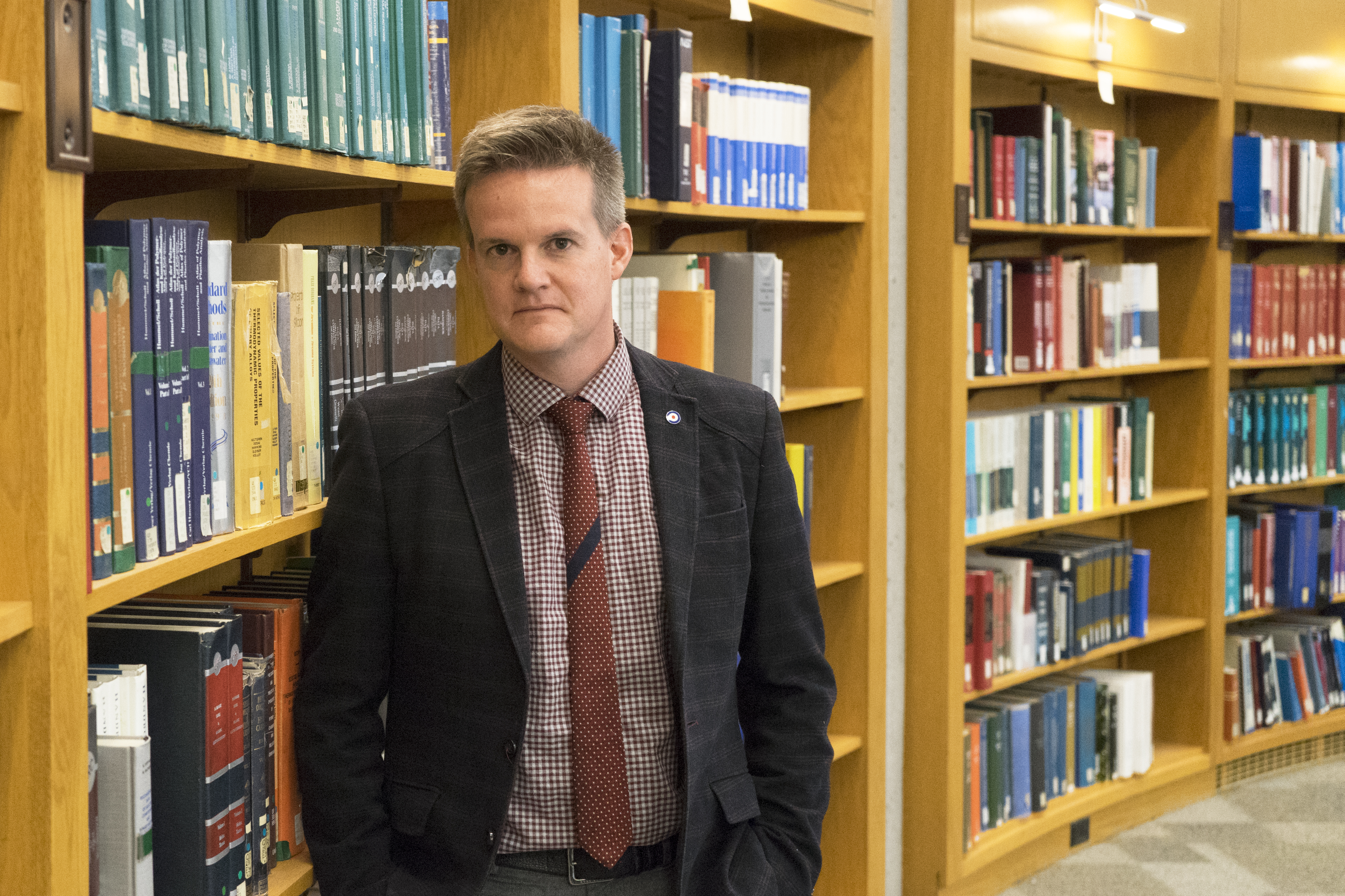 Professor Jason Anderson stands in the Engineering Library at U of T